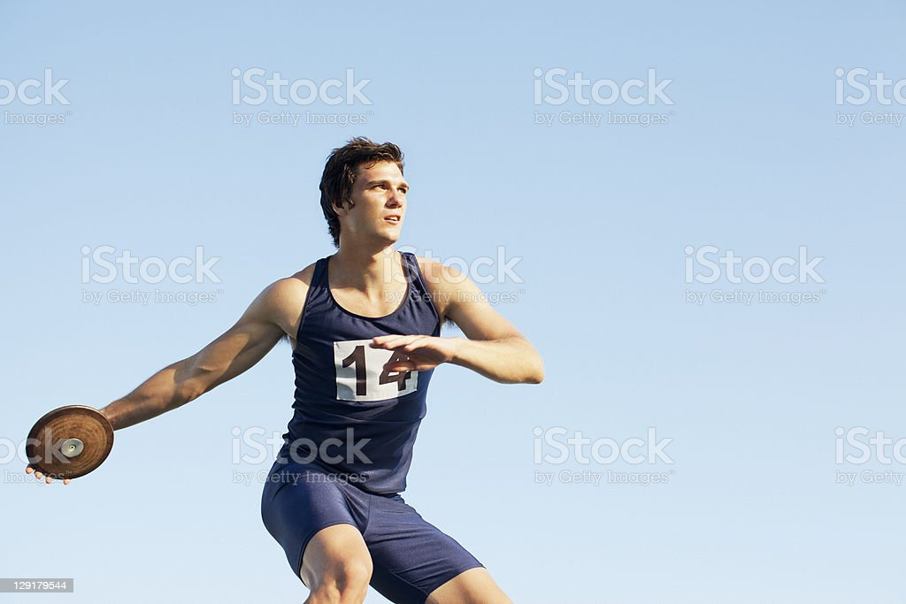 Man throwing discus against sky royalty-free stock photo