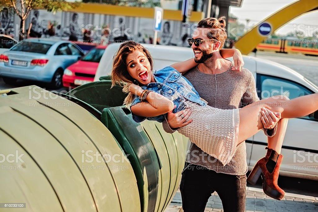 Man throwing girl in the garbage stock photo