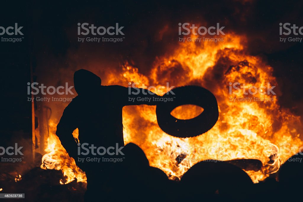 Man throws a tire into a fire stock photo