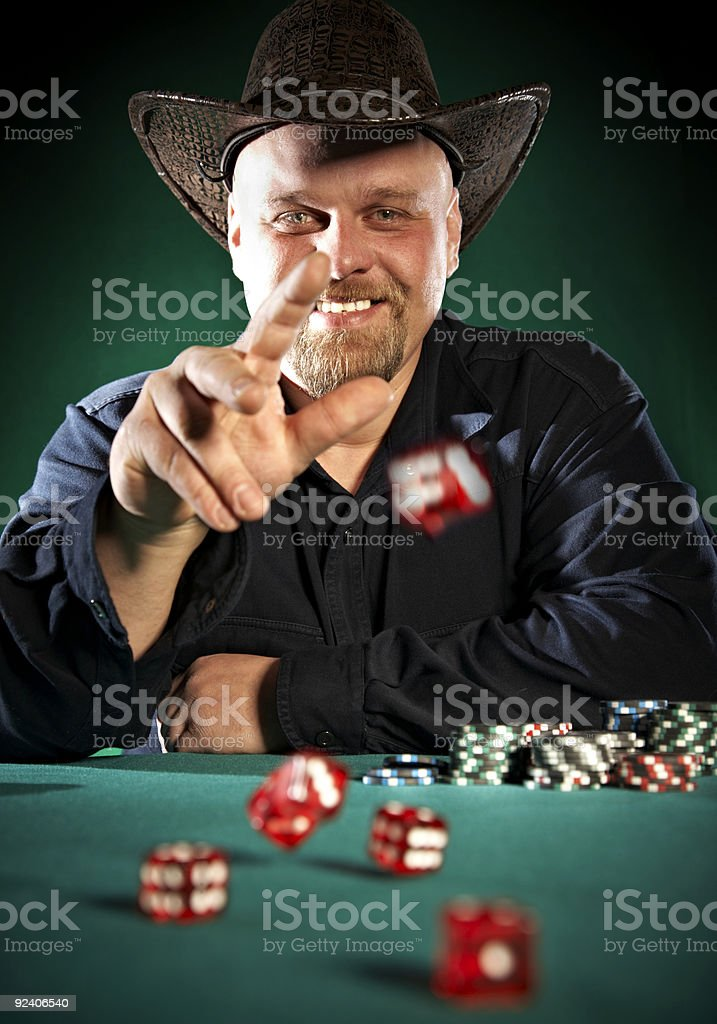 man throws dice on a green background stock photo