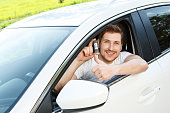 Man thumbing up in car with alarm system