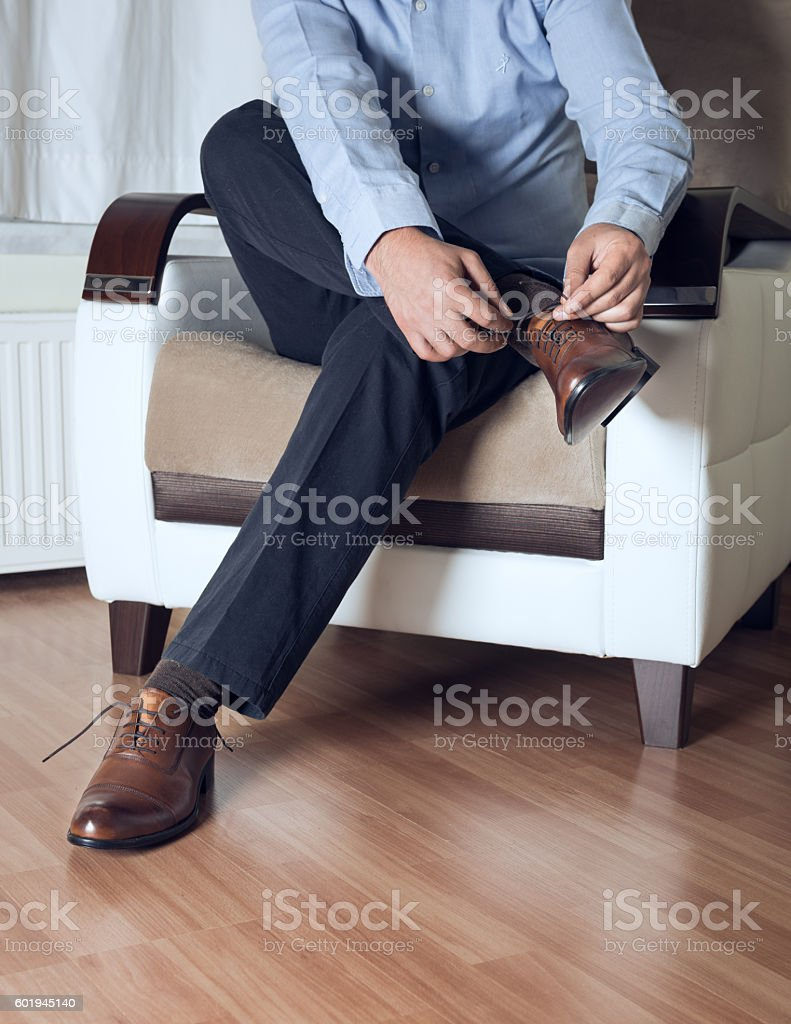 Man ties his brown shoes stock photo