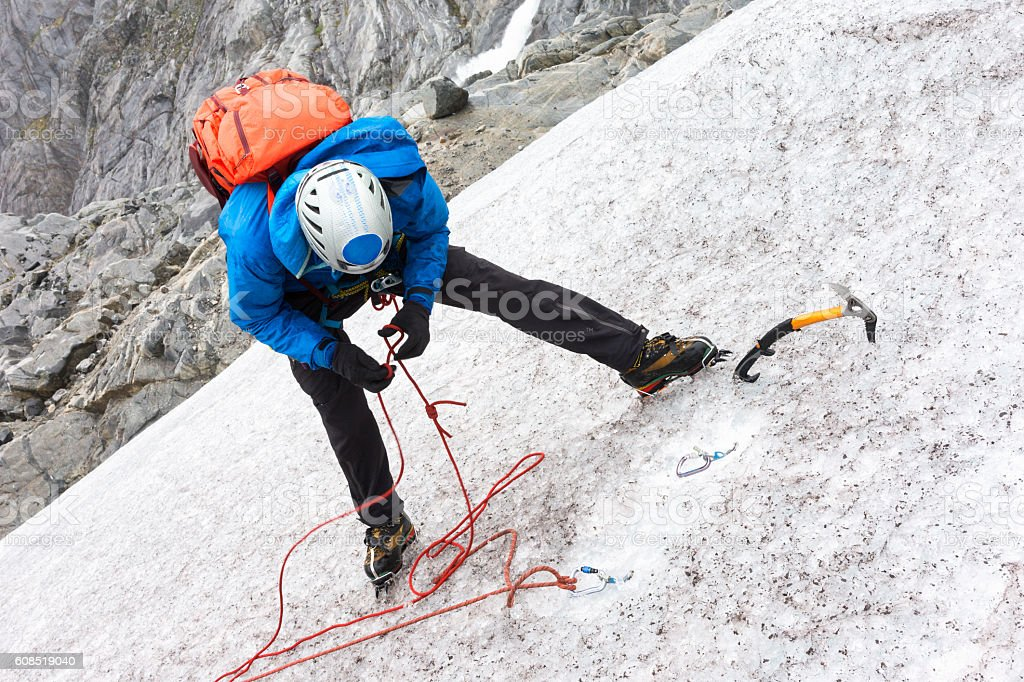Man ties knot in rope for rappelling stock photo
