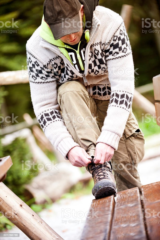 Man ties the shoelace of his hiking boot stock photo