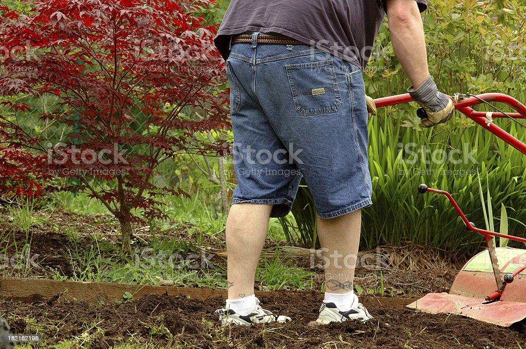 Man tilling the garden stock photo