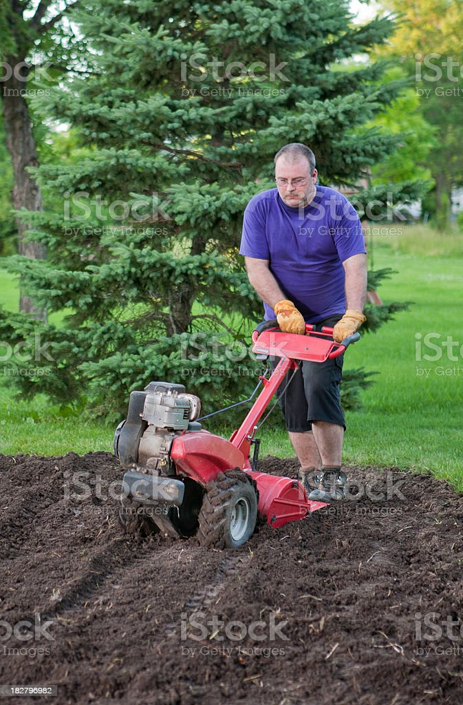 man tills garden with rototiller royalty-free stock photo