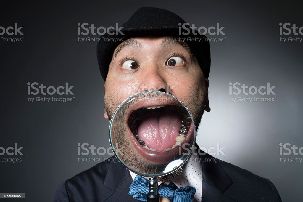 Man to be examined state of teeth with magnifying glass stock photo