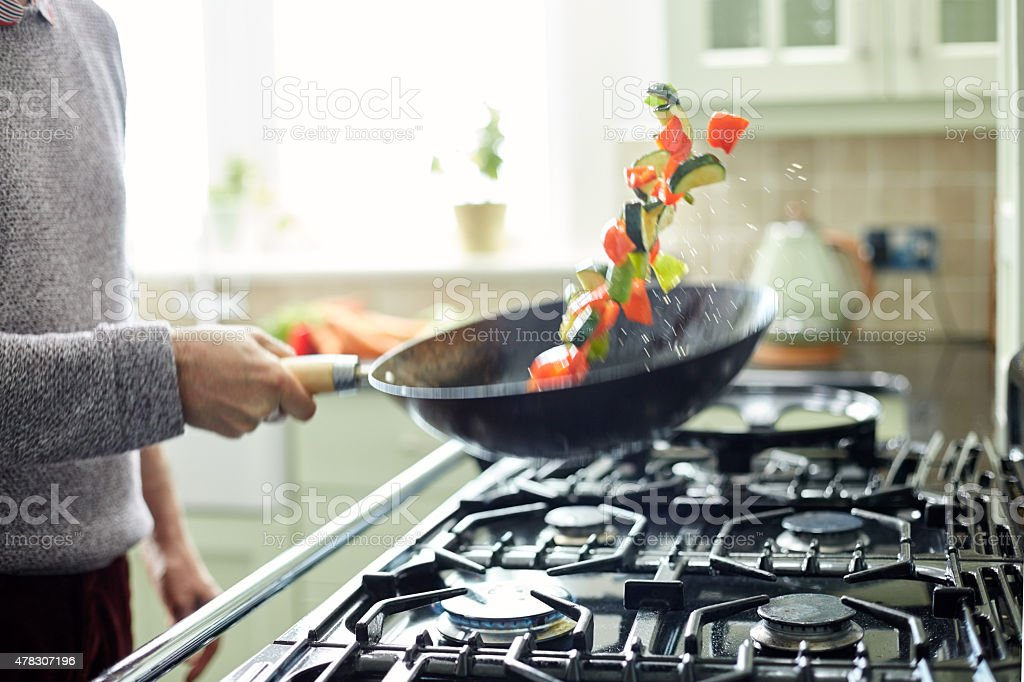 Man tossing fresh vegetables in saucepan at kitchen stock photo