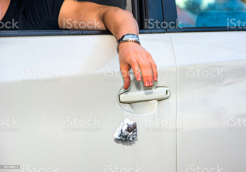 Man Tossing Litter from Open Car Window stock photo