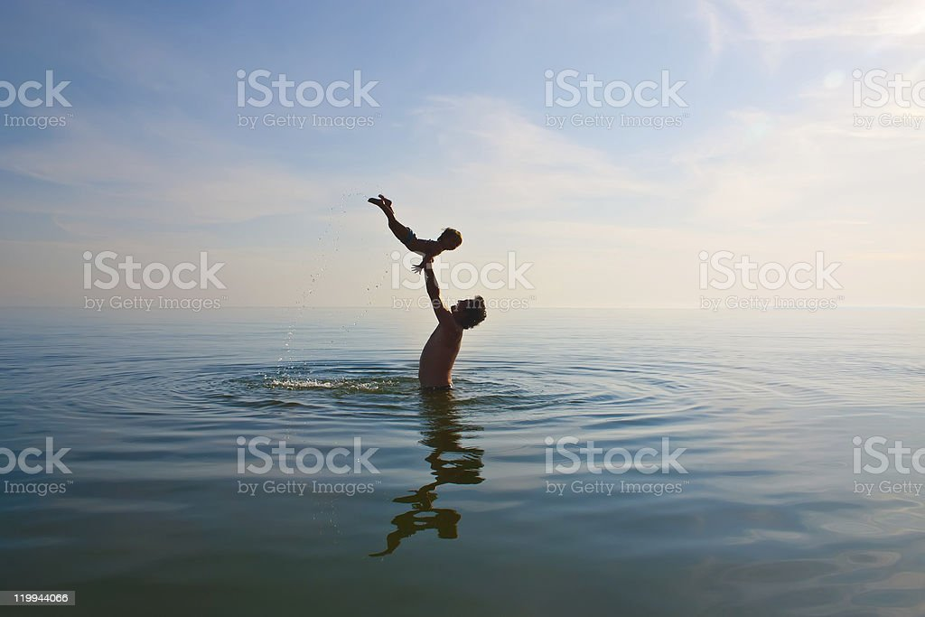 Man tossing up child in the sea royalty-free stock photo