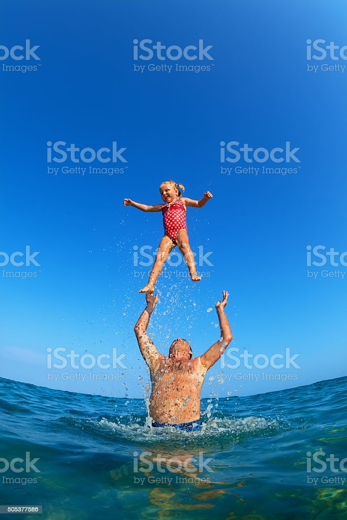 Man tossing up child with water splashes in beach stock photo