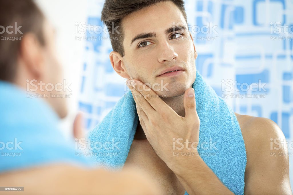Man touching his face after shaving stock photo