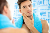 Man touching his face after shaving