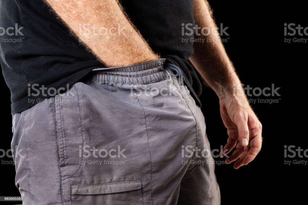 Man touching his genital area through his trousers stock photo