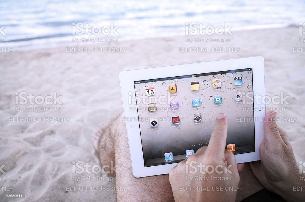 Man Touching iPad2 Homescreen At The Beach royalty-free stock photo