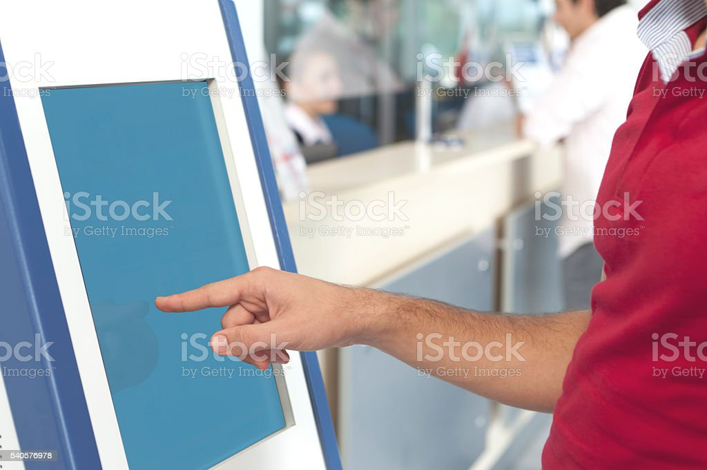 man touching screen kiosks stock photo