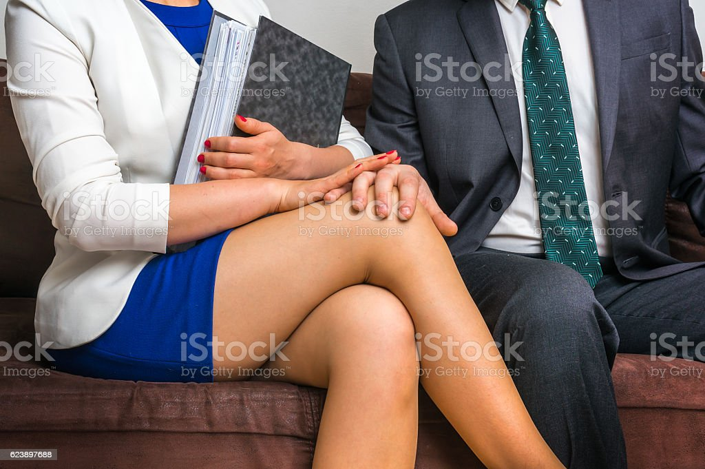 Man touching woman's knee - sexual harassment in office stock photo