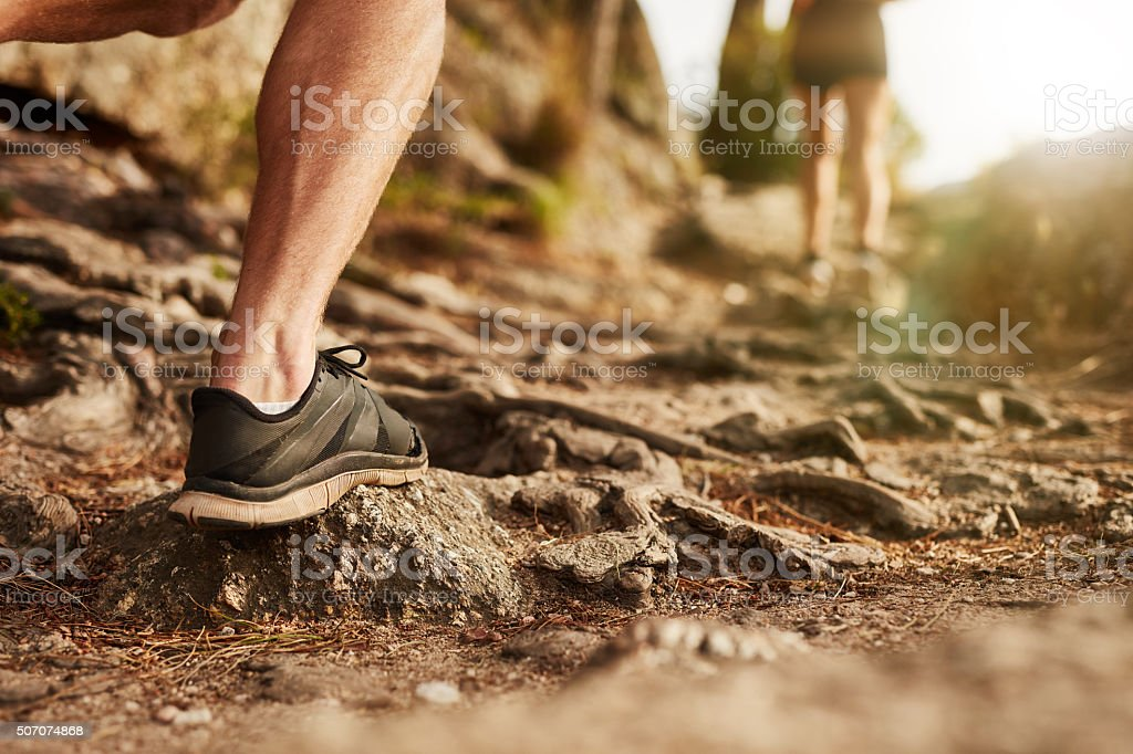 Man trail running on rocky terrain stock photo
