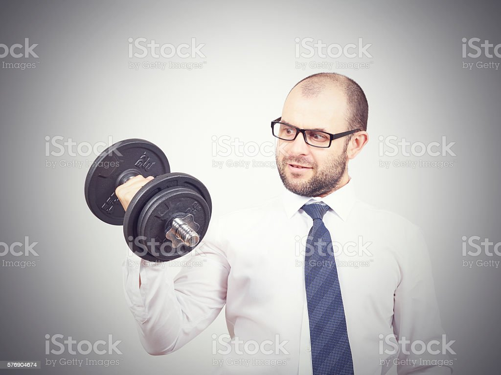 Man Trained businessman raises dumbbell. stock photo