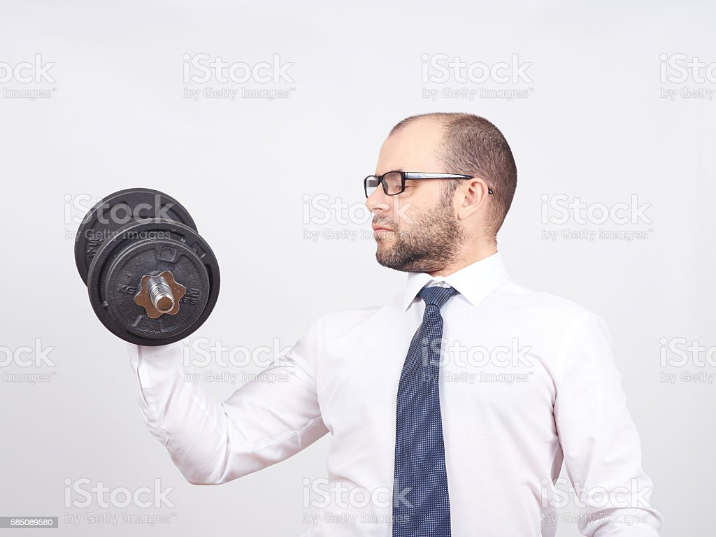 Man Trained businessman raises dumbbell. stock photo