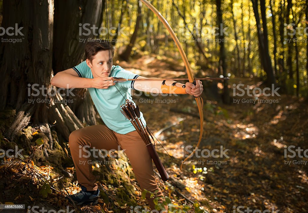Man training in wood with bow and arrow. stock photo