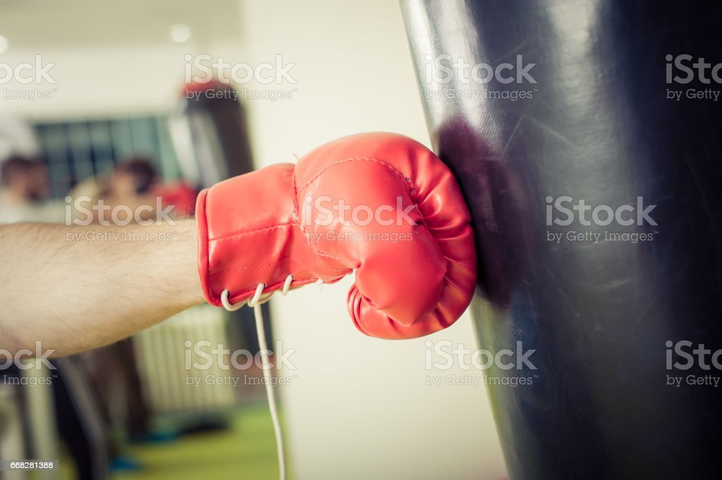 Man training on a punching bag in the gym stock photo