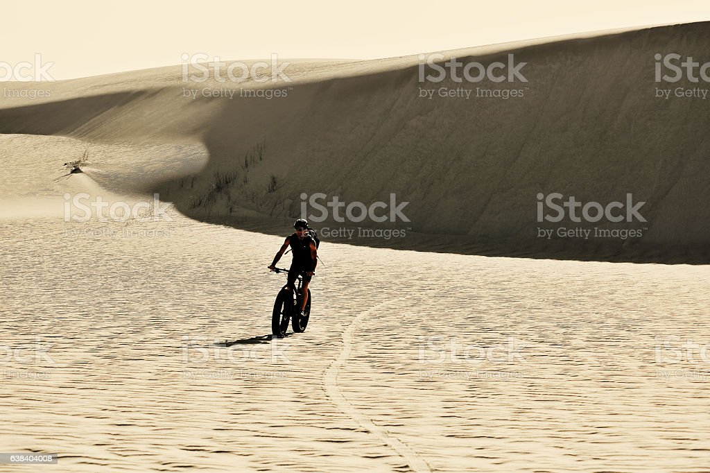 Man trains on a bicylce in the sand dunes stock photo