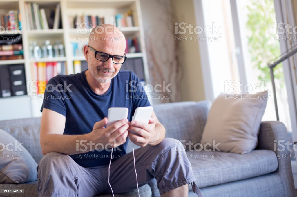 Man transferring data between his old and new smart phones stock photo