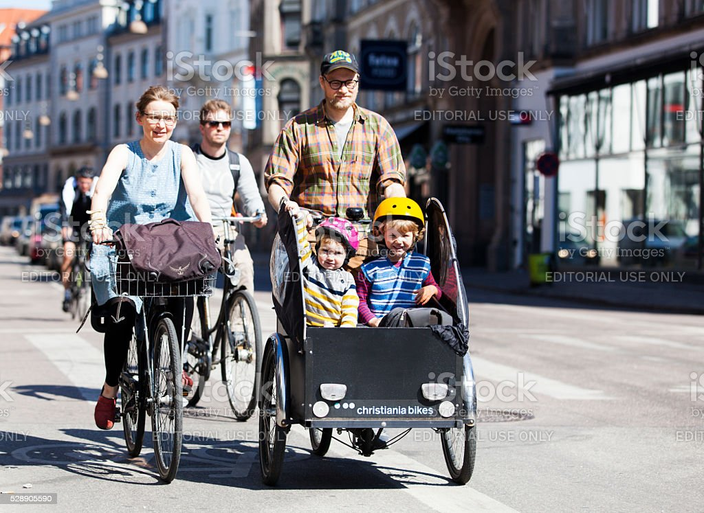 Man transporting two children on a bicycle fitted with box stock photo