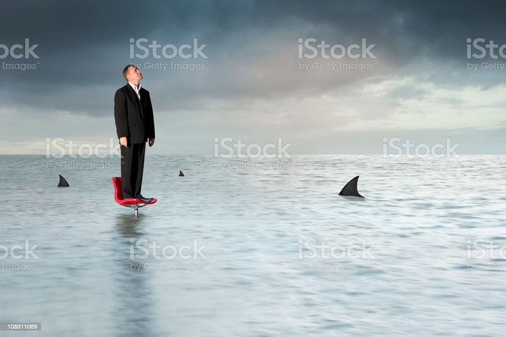 Man trapped in the middle of a sea of sharks on chair stock photo