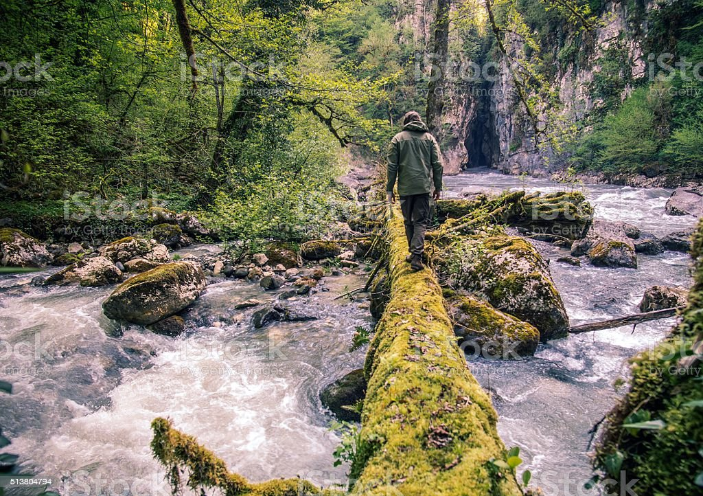 Man Traveler crossing river on log outdoor stock photo