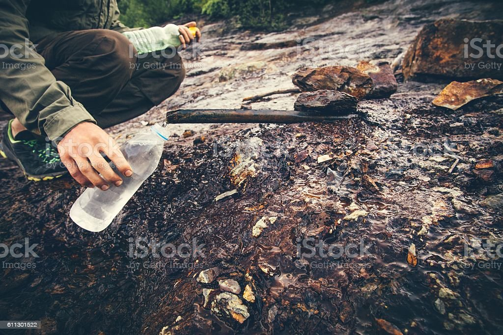 Man Traveler hand taking water in bottle from mineral well stock photo