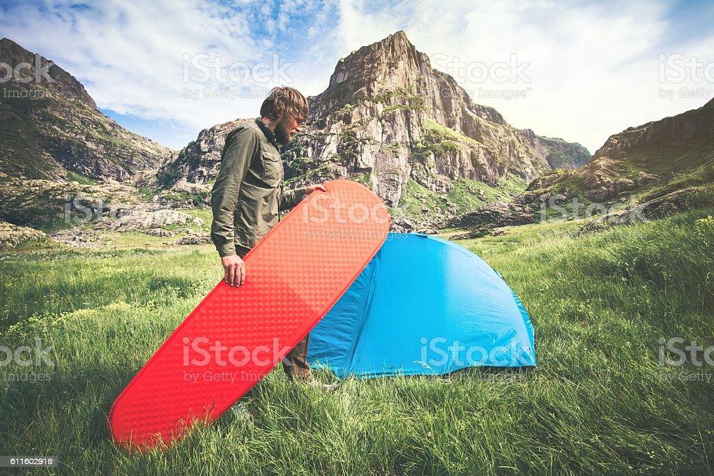 Man Traveler holding red mattress camping equipment Travel Lifestyle stock photo