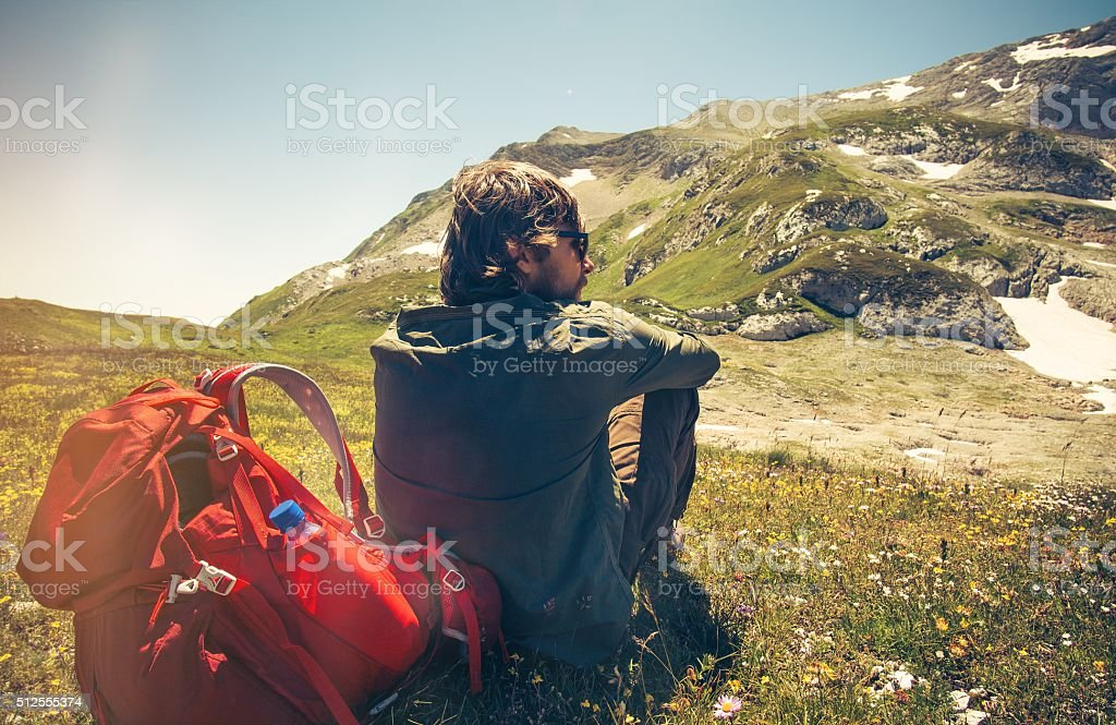 Man Traveler with backpack relaxing outdoor Travel Lifestyle stock photo