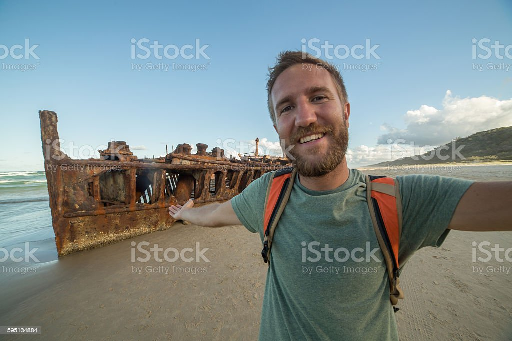Man traveling takes selfie portrait with shipwreck on Fraser Island stock photo