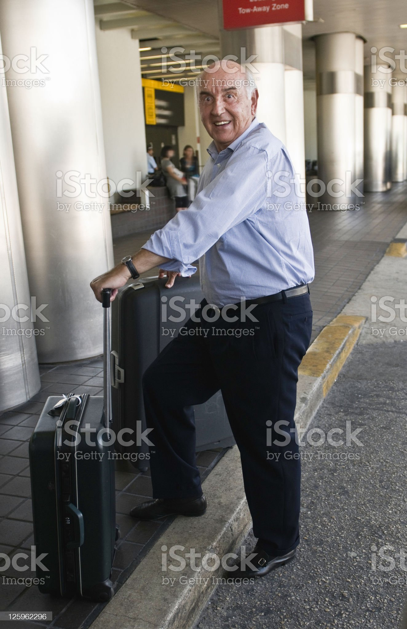 A man travelling through an airport with a luggage trolley. royalty-free stock photo
