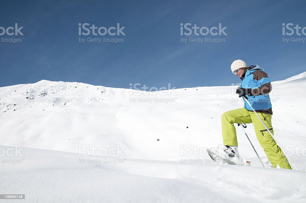 A man trekking in the snow with snow shoes stock photo