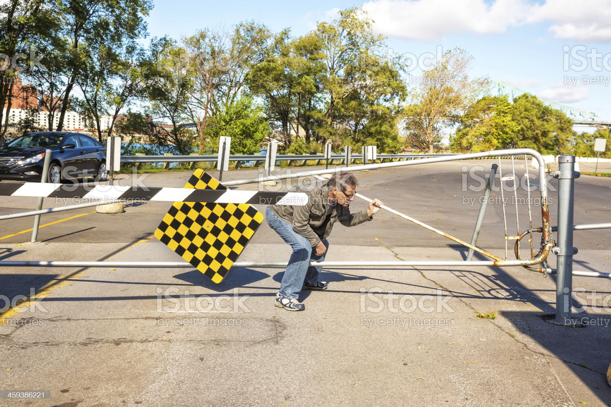 Man tries to go under road crossing barrier royalty-free stock photo