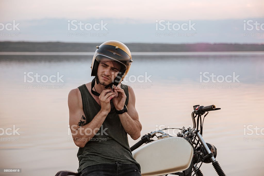 Man tries to put off his helmet sitting on motorcycle stock photo