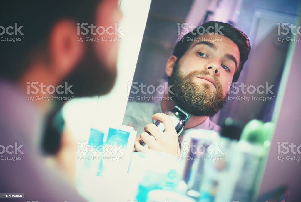 Man trimming beard in front of a mirror. stock photo