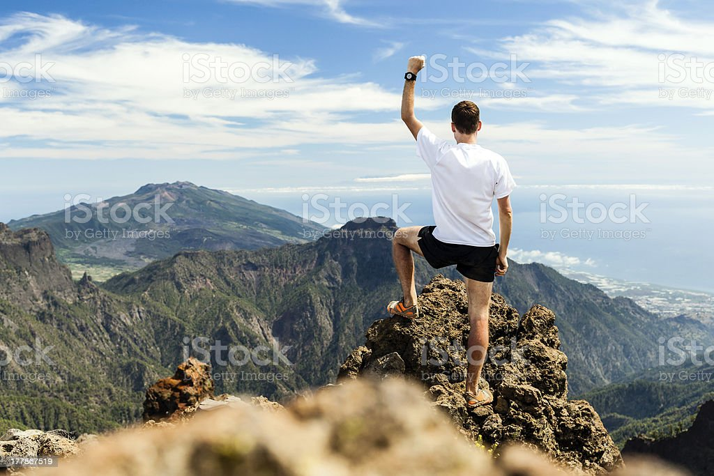 Man triumphantly at the top of a mountain stock photo