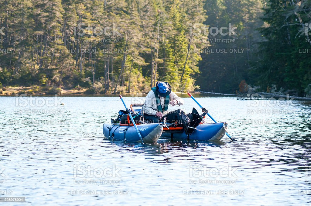 Man Trout Fishing on Cleawox Lake in Inflatable Pontoon Boat stock photo