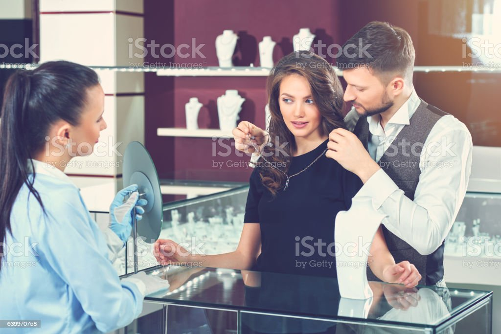 Man trying necklace for his wife at jewelry store. stock photo