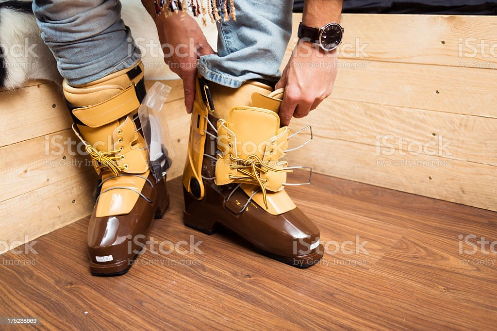 man trying on a skiing boots in ski store stock photo