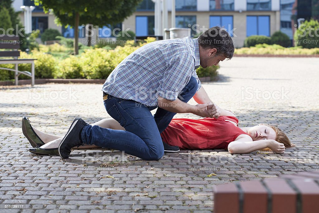 Man trying to help unconscious woman stock photo