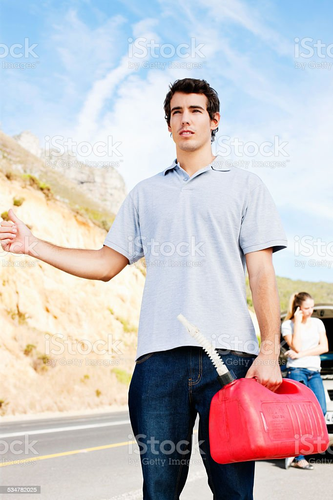 Man Trying to Hitchhike for Gas stock photo