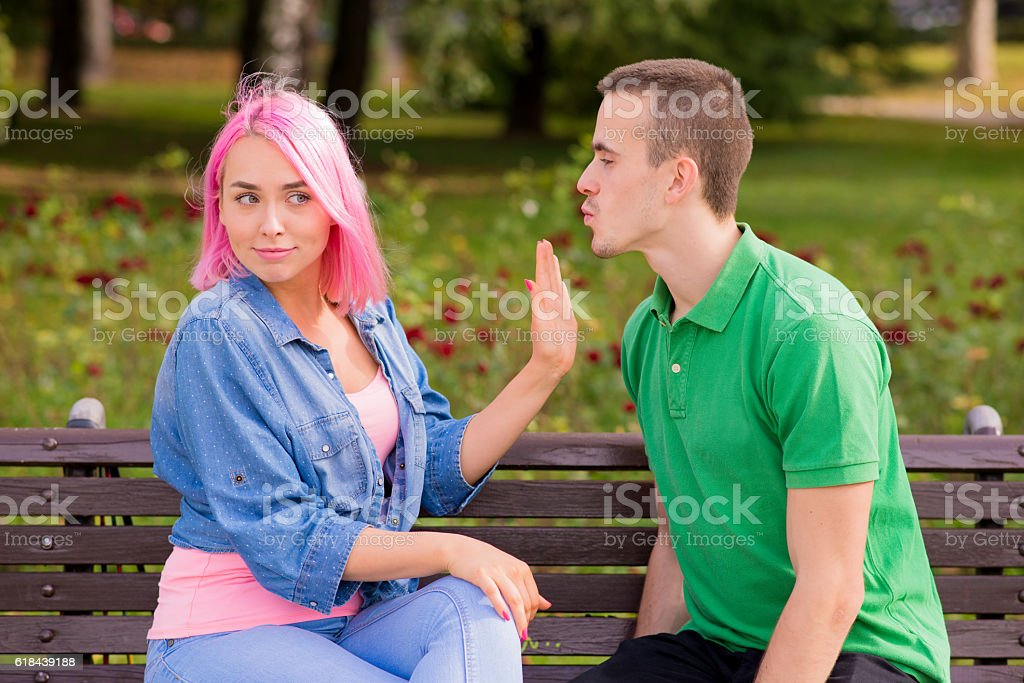 Man trying to kiss a woman and she is rejecting stock photo