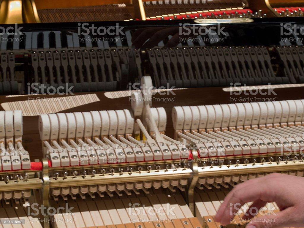 man tunes a piano stock photo