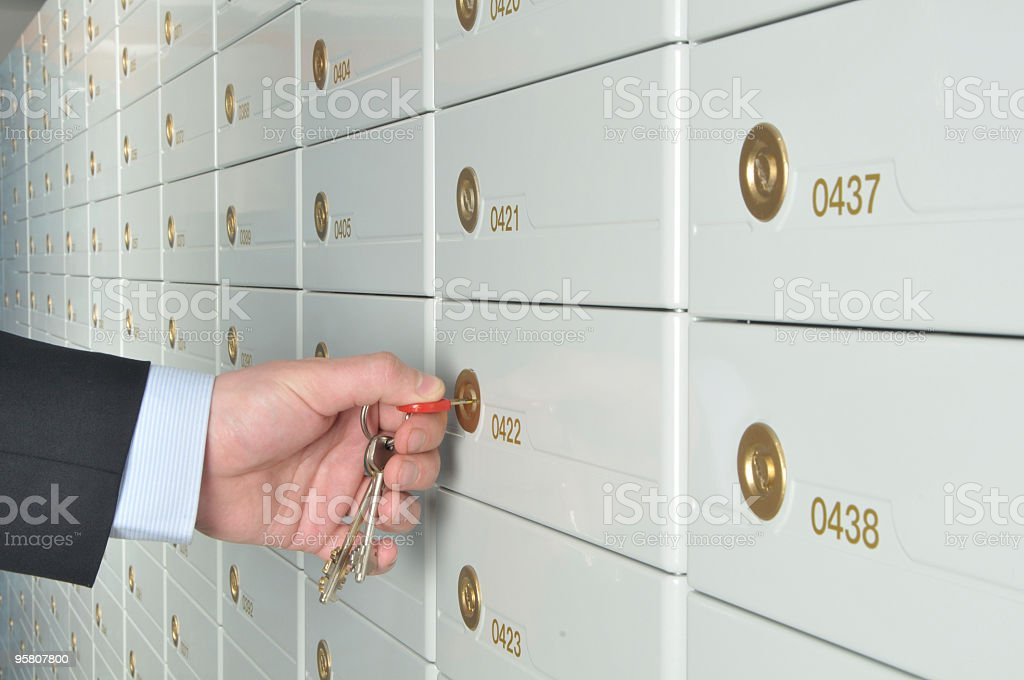 A man turning a key to a safe deposit box stock photo