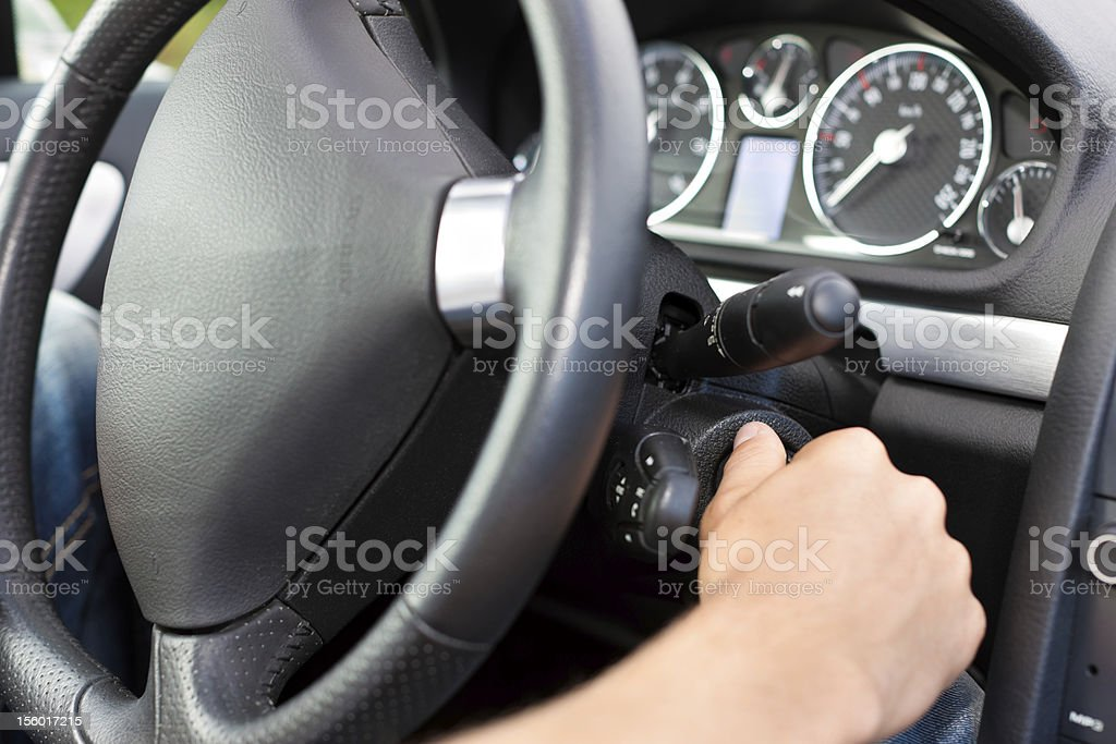 Man turning the ignition key of his car stock photo